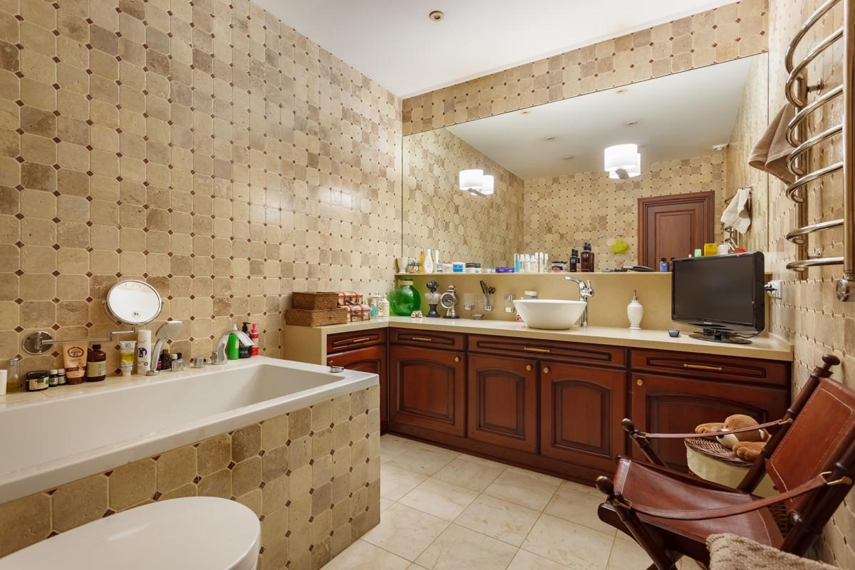 Стилистику гранжа продолжает интерьер ванной комнаты. Крупная мозаичная плитка из натурального мрамора, поверхность которого обработана травлением, благодаря чему мрамор получил явную текстуру старения. Под столешницей коричневые деревянные дверцы встроенного шкафа. Сама столешница с умывальником больше производит впечатление стола, чем традиционной столешницы с умывальником.