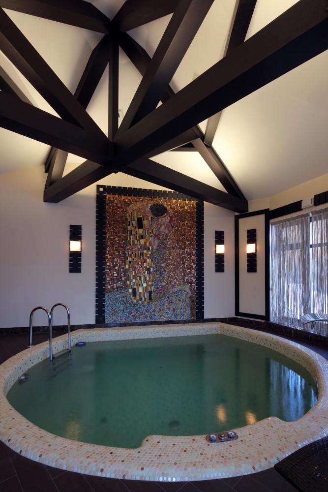 Чаша бассейна, выстланная нежной мозаикой, симметрично передаёт форму самого помещения, а тёмный дощатый пол «пляжа» гармонично перекликается с декоративной звездой на потолке, оконными рамами и тёмными шезлонгами. Центральную стену бассейна занимает мозаичная репродукция самой популярной картины Густава Климта «Поцелуй».